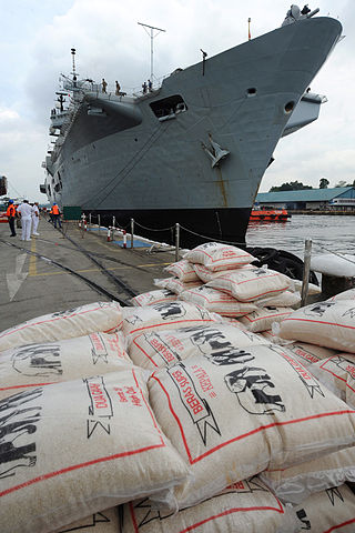 HMS Illustrious loading supplies in Singapore. Source: Wikimedia Commons/MoD
