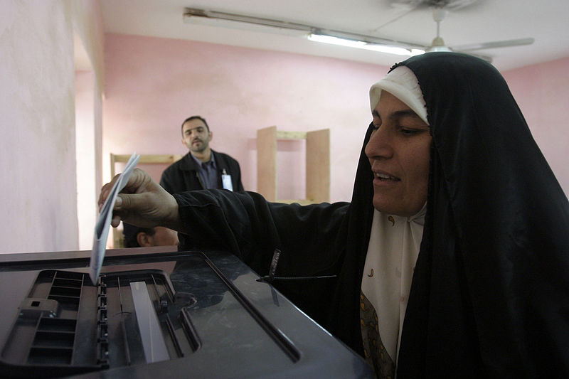 An Iraqi woman votes in Rawah in 2005. Photo source: Lance Cpl. Shane S. Keller via Wikimedia Common