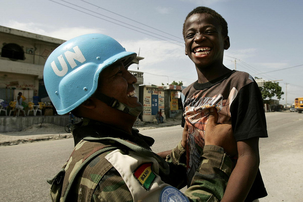 A Bolivian peacekeeper plays with a child in Cité Soleil, Haiti. Photo Source: United Nations Photo via Flickr Creative Commons