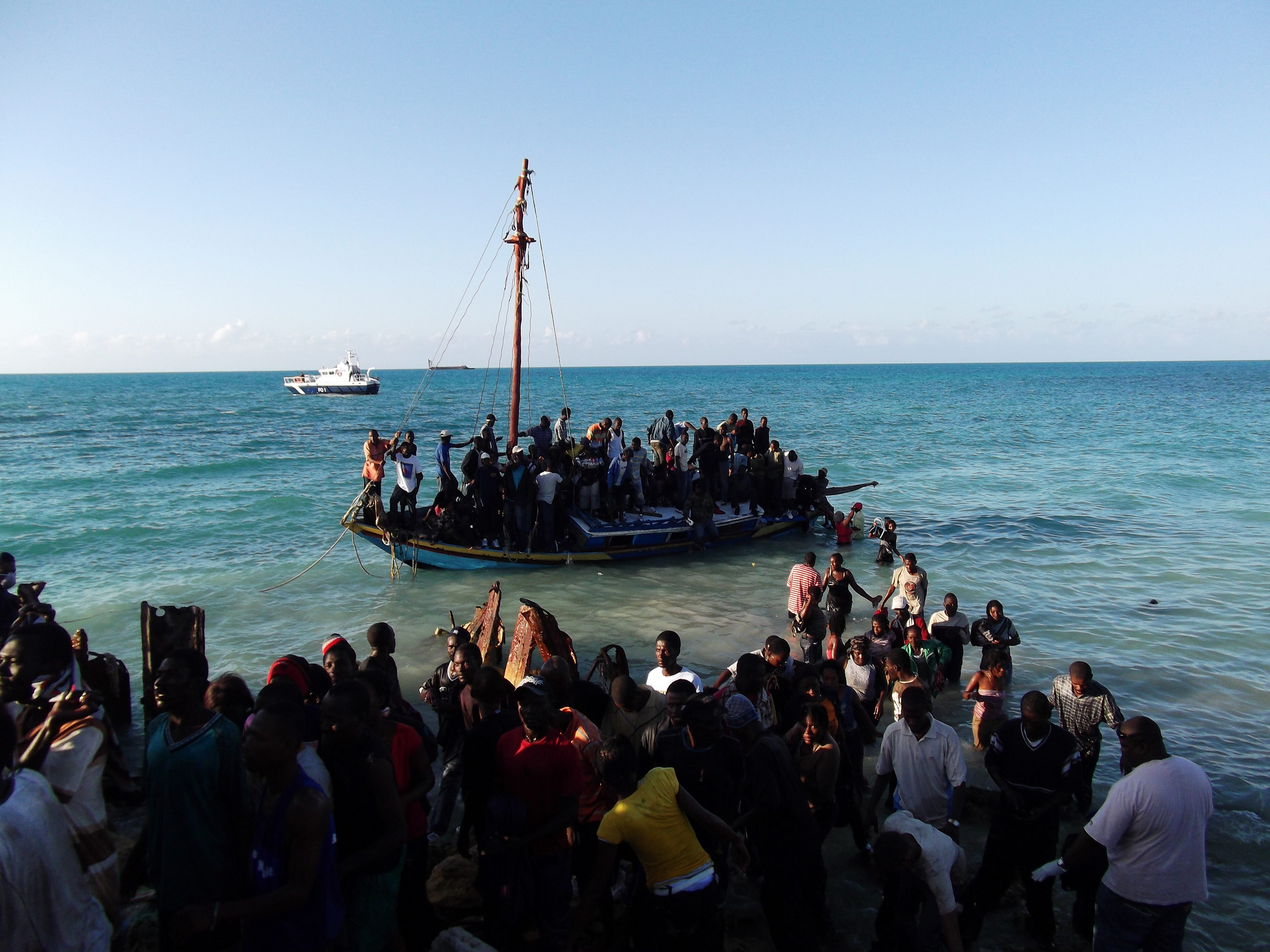 Residents of the Turks and Caicos Islands in the Caribbean assist passengers on an overcrowded sloop. The boat had just arrived from Haiti carrying 139 people. UNHCR / 25 February 2011