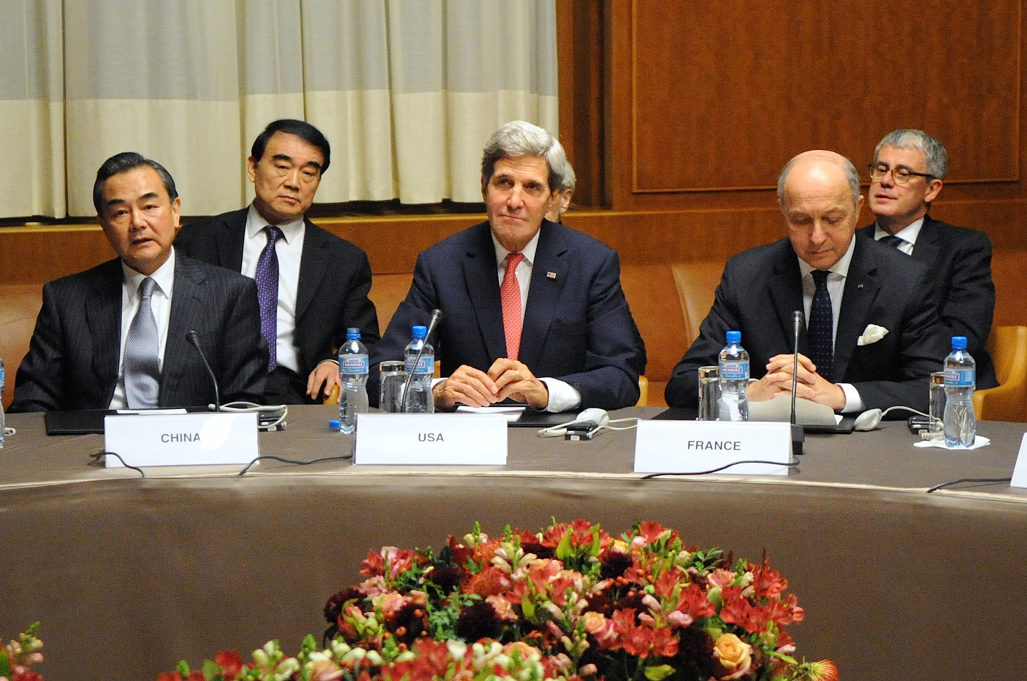 U.S. Secretary of State John Kerry sits between Chinese Foreign Minister Wang Yi and French Foreign Minister Laurent Fabius at the United Nations Headquarters after the P5+1 member nations concluded a nuclear deal with Iran in Geneva, Switzerland, on November 24, 2013 via Flickr Commons